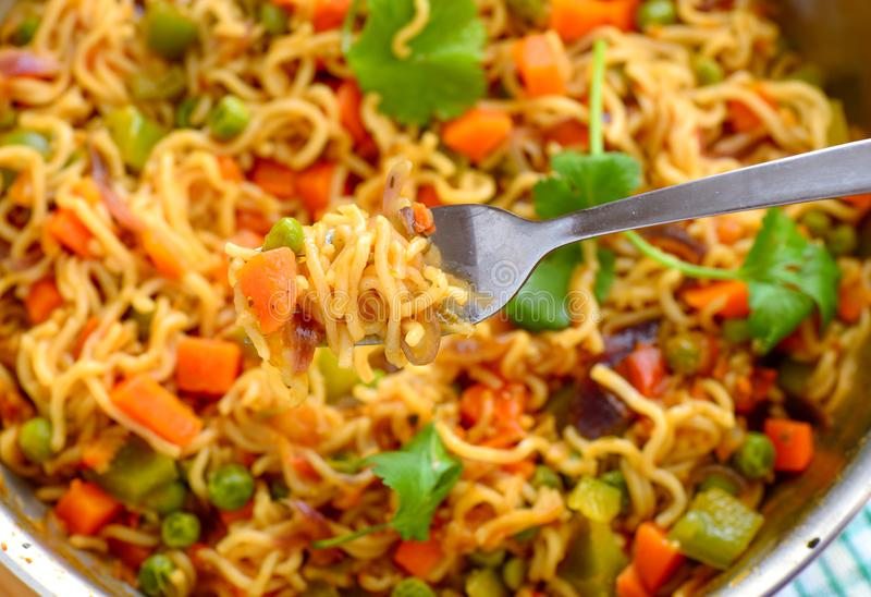 Maggi noodles cooked with vegetables. Vegetable maggi cooked with peas,beans,carrots,capsicum eaten for breakfast or evening snack stock photography