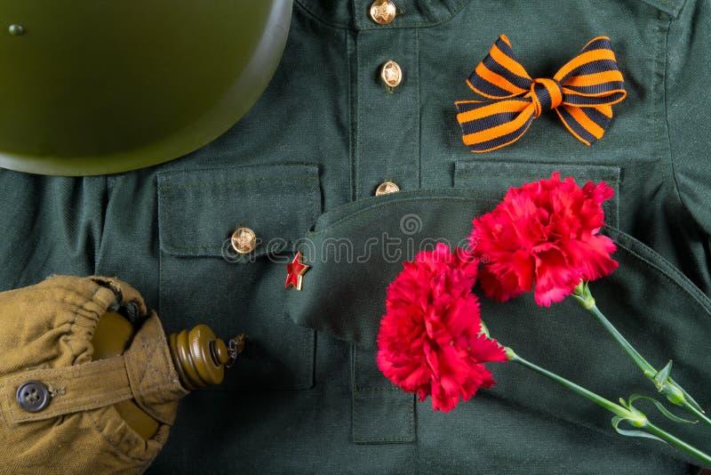 9 maggio con un nastro di St George e due garofani, sui precedenti dei vestiti militari fotografia stock