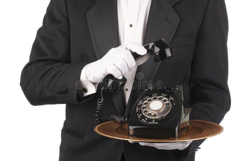 Maggiordomo con il telefono sul cassetto fotografia stock