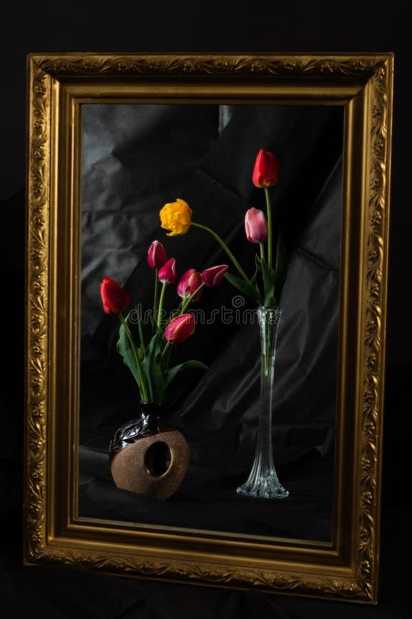 Magia astratta Il tulipano fiorisce nella stanza scura che riflette in specchio immagini stock