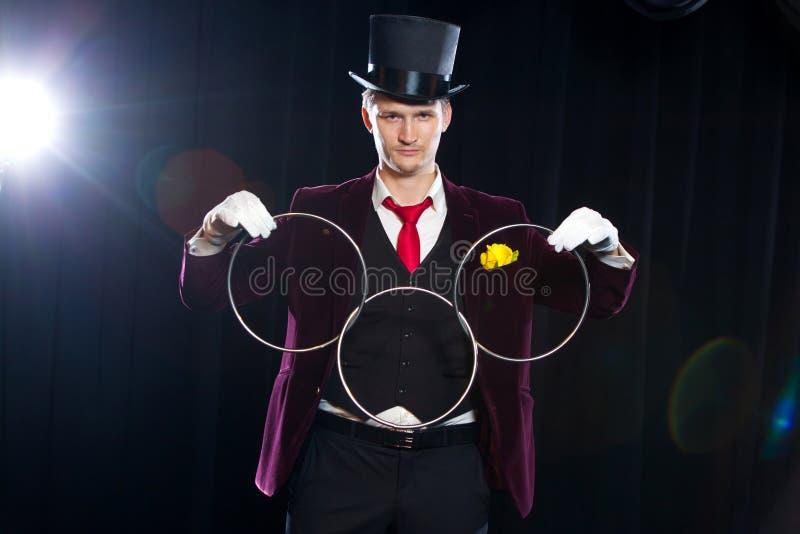Magia, funcionamiento, circo, concepto de la demostración - el mago en truco de la demostración del sombrero de copa con el lazo  foto de archivo libre de regalías