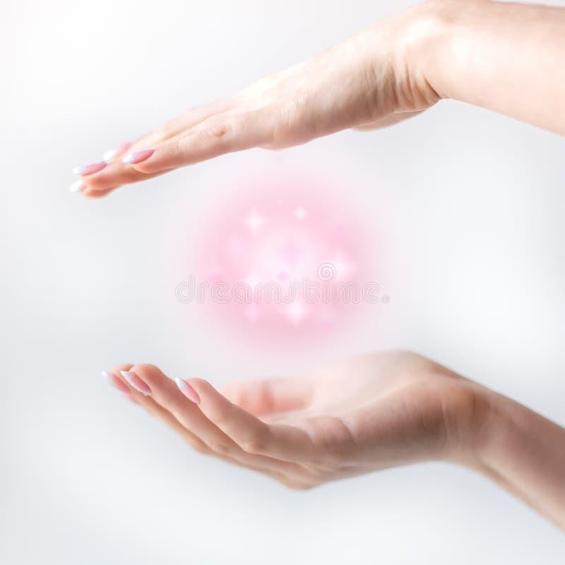 magia rosada en el aire entre las manos fotos de archivo libres de regalías