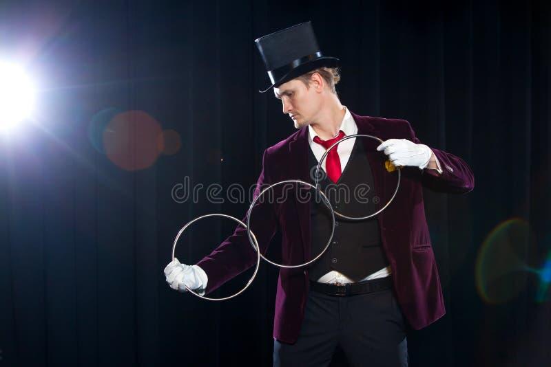 Magia, występ, cyrk, przedstawienia pojęcie - magik w odgórnego kapeluszu seansu sztuczce z zazębianiem dzwoni zdjęcie stock