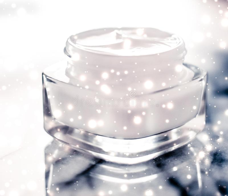 Magic beauty face cream and glitter glow on blue marble stone in winter holiday time, skincare moisturizer and luxury spa. Anti-age product, facial care and royalty free stock images