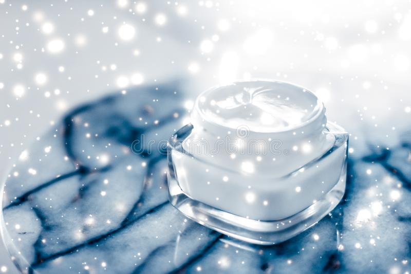 Magic beauty face cream and glitter glow on blue marble stone in winter holiday time, skincare moisturizer and luxury spa. Anti-age product, facial care and royalty free stock photography