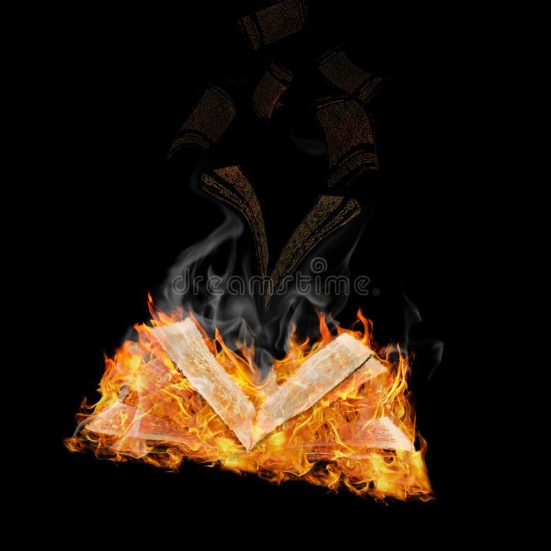 Magic book. Open magic book in flame against black background stock photo
