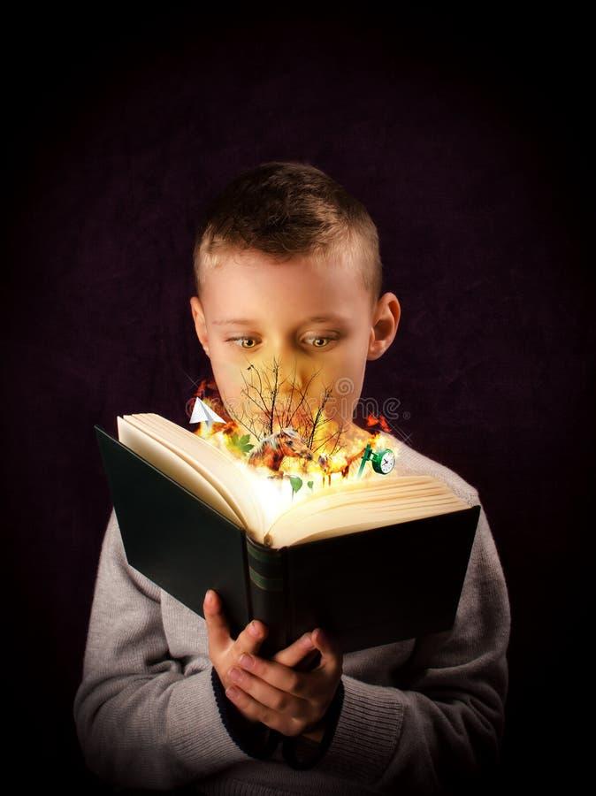Magic book. Young boy reading and looking at a magic book stock image