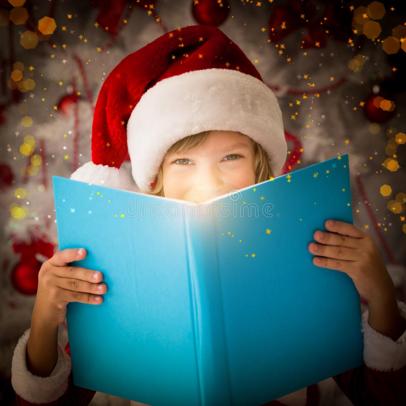 Magic book concept. Happy child opening magic Christmas book. Xmas holiday concept stock photography