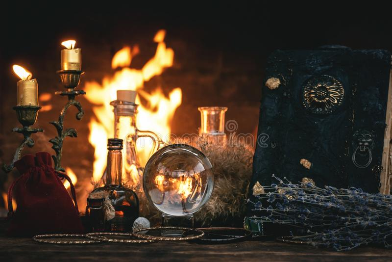 Magic book and Crystal ball. Crystal ball, magic book, magic potion and other wizard accessories on a table on a burning fire background, spell, reading, future stock image