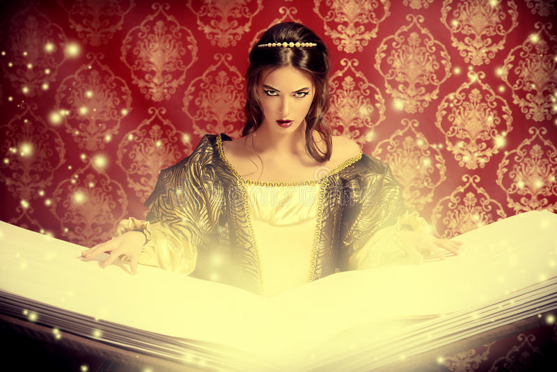 Magic book. Fairy beautiful witch reads magic book of spells. Vintage style. Renaissance. Barocco. Halloween royalty free stock image