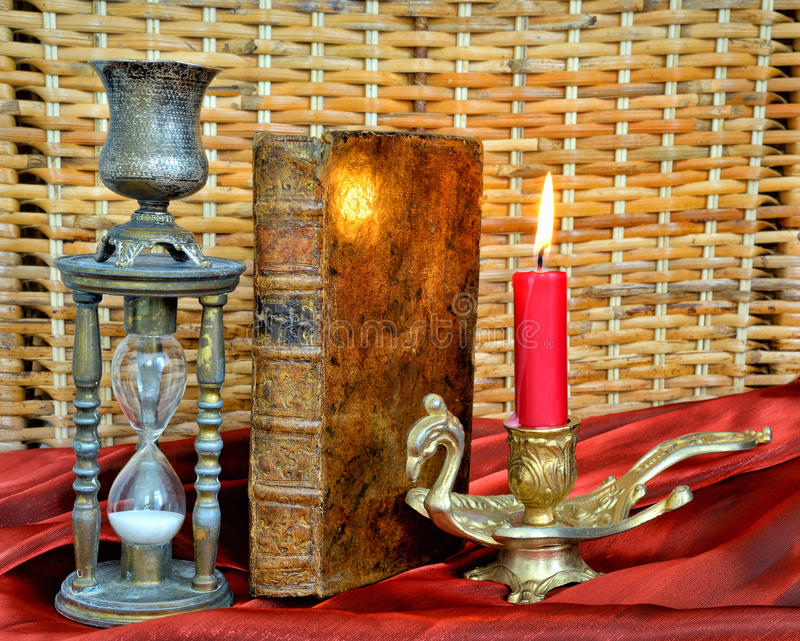 Magic book, firing candle and hourglass stock image