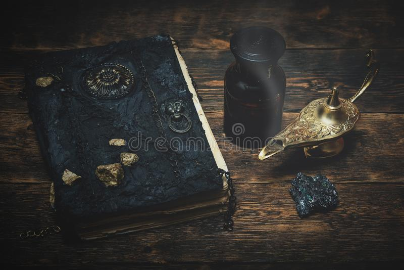 Genie lamp and a magic book. A magic book and a golden lamp on a wooden table board background stock image