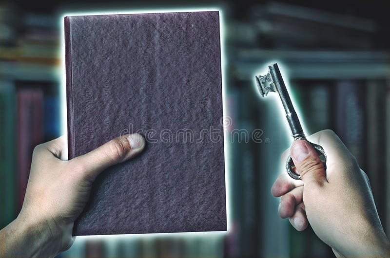 Magic book and key with magic light. In hand against the shelves with books, search for information in an book, a reading room in the library and study. The stock photos