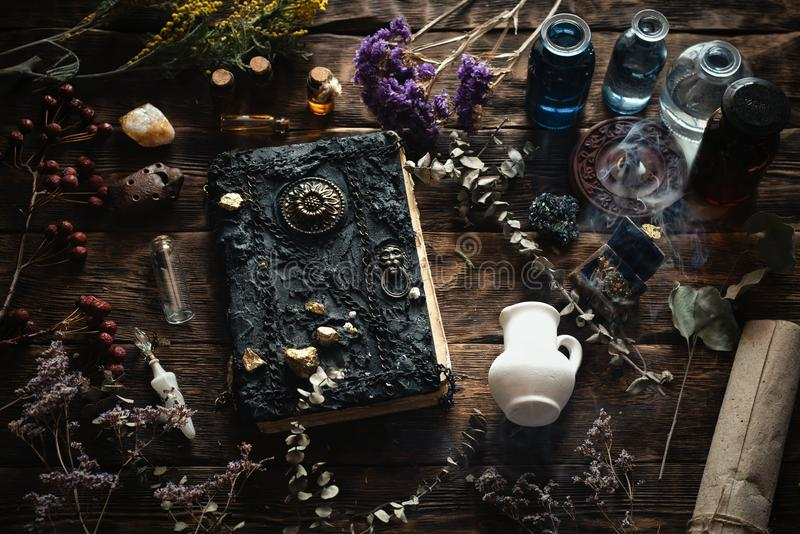 Magic book. Magic recipe book and a magic potions on a table. Witchcraft background with copy space. Druid or witch doctor table royalty free stock images