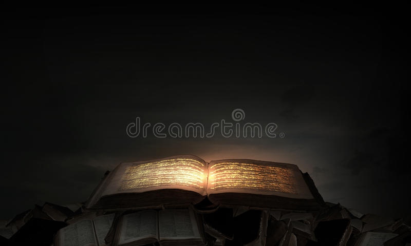 Magic book. Old black magic book with lights on pages royalty free stock photo
