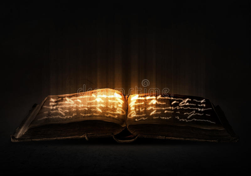Magic book. Old black magic book with lights on pages stock image