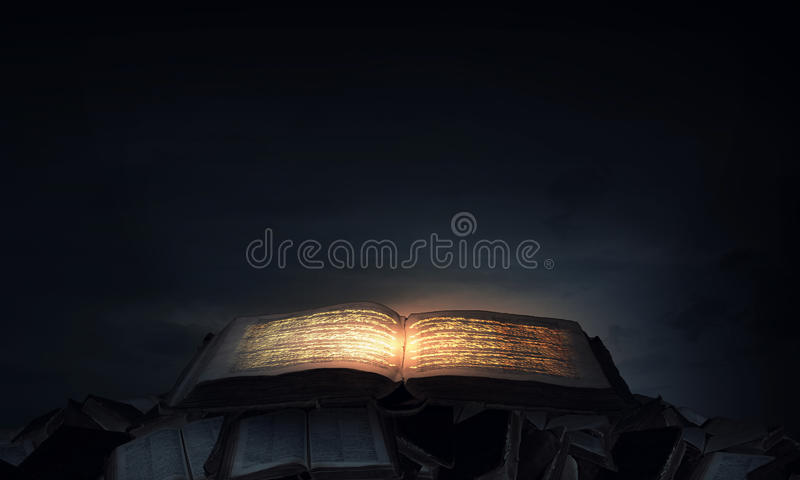 Magic book. Old black magic book with lights on pages stock images