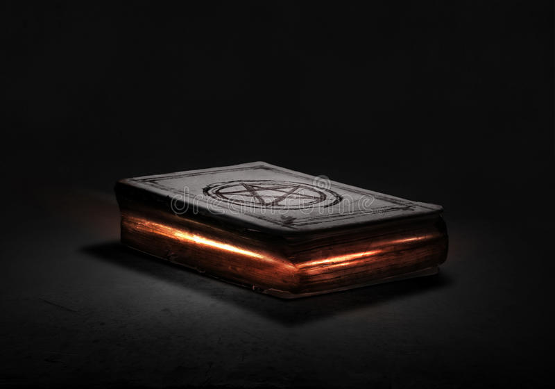 Magic book. Old black magic book with lights on pages royalty free stock image
