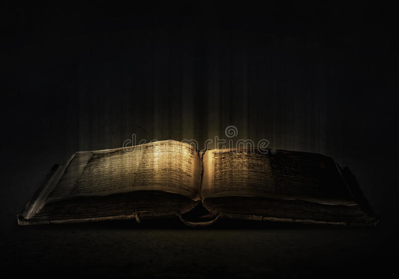 Magic book. Old black magic book with lights on pages royalty free stock images