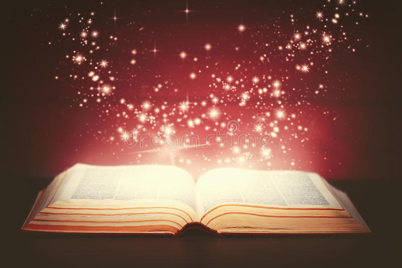Magic book open. And the light from it stock images