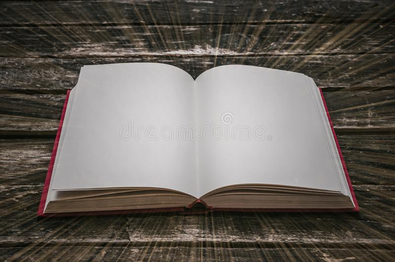 Magic book. Open magic book with empty blank pages and rays of light around it on the table royalty free stock photography