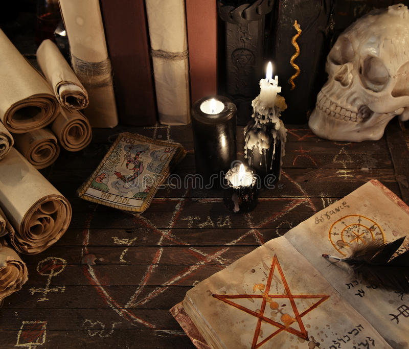 Magic book with pentagram, the tarot cards and candles on wooden planks royalty free stock photography