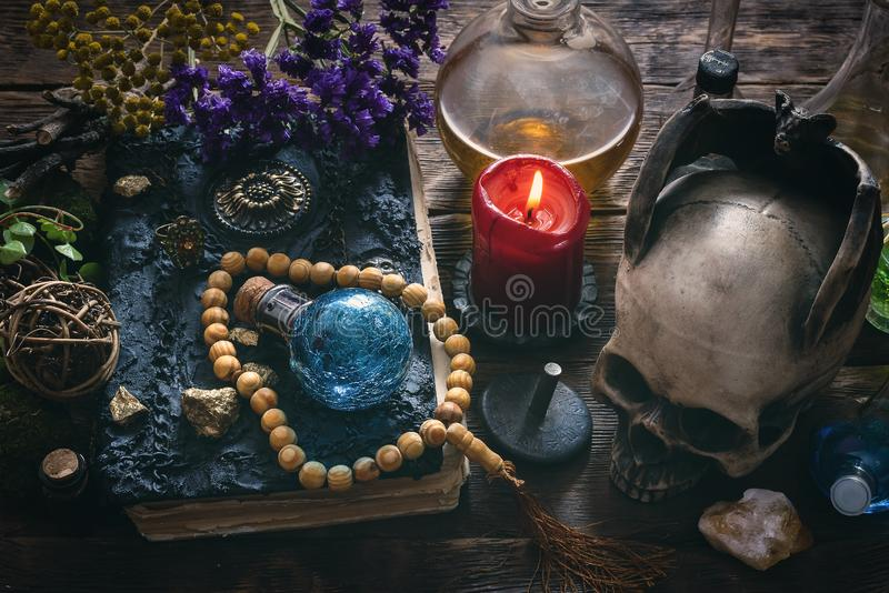 Magic book. Spell book, magic potions and other various witchcraft accessories on the wizard table background royalty free stock photos
