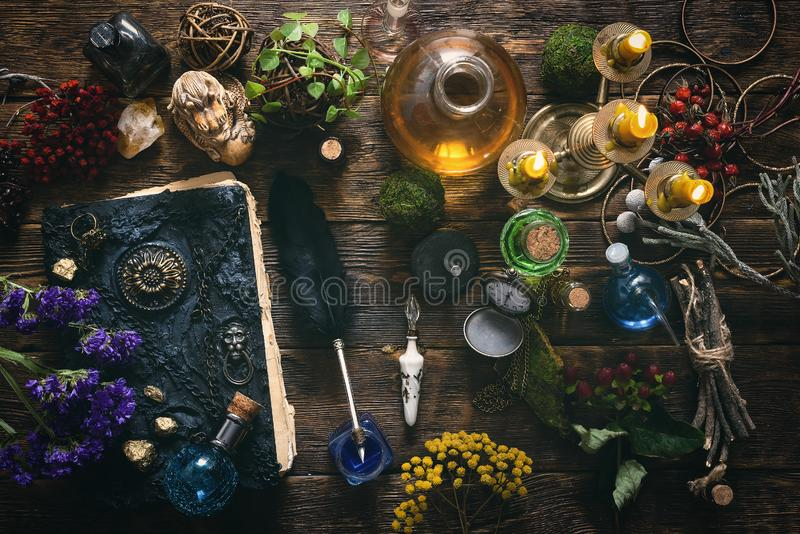Magic book. Spell book, magic potions and other various witchcraft accessories on the wizard table background stock photo