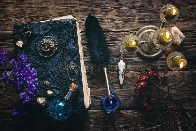 Magic book. Spell book, magic potions and other various witchcraft accessories on the wizard table background royalty free stock image