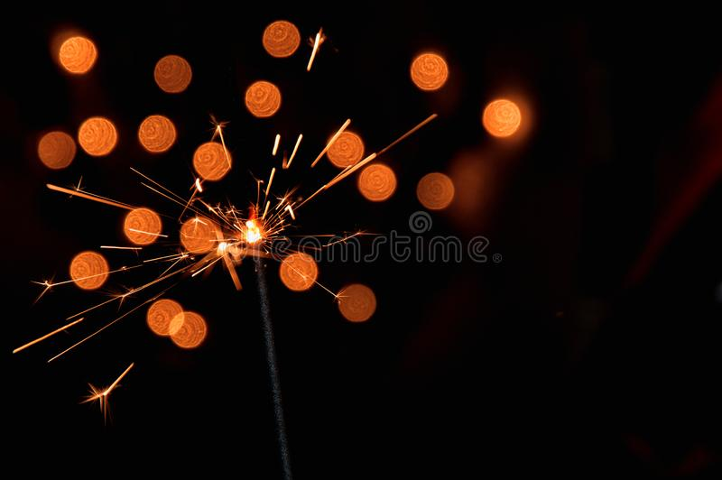 Magic burning sparkler. Dark background with blurred lights of Christmas garland. Copy space on the right. royalty free stock image