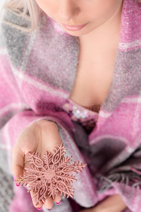 Magic christmas coziness comfort blanket snowflake. Magic of christmas and winter coziness and home comfort. woman holding a rose gold shiny snowflake in hands stock photo