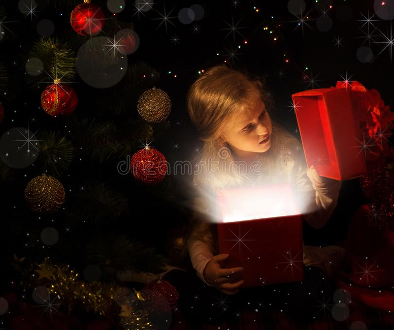The magic of Christmas. The little girl in new year location looks in a gift box stock images