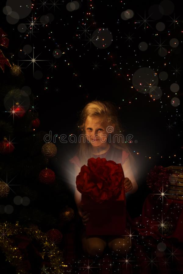 The magic of Christmas. A little girl opens the big red gift. The magic of Christmas. A little girl opens big red gift royalty free stock image