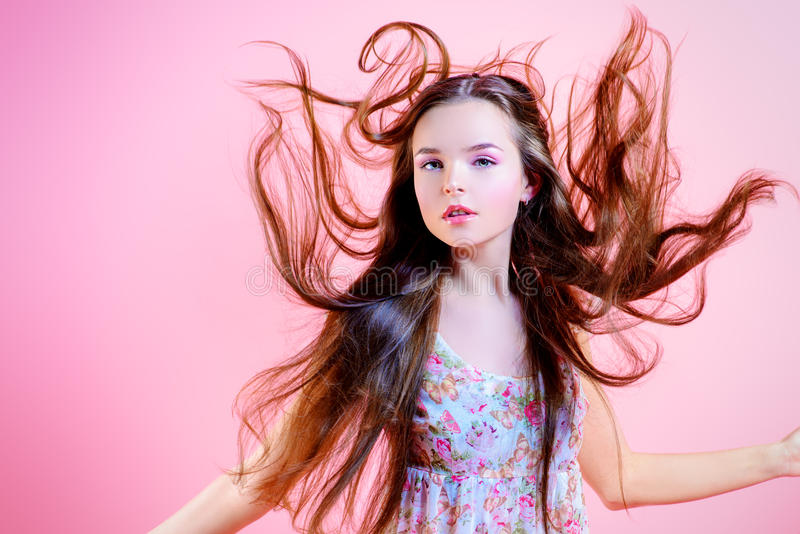 Magic fly. Elegant girl with natural make-up and beautiful long hair in motion posing over pink background. Fashion. Hairs royalty free stock images