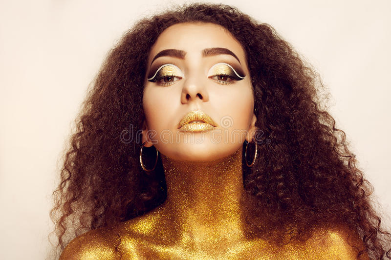 Magic Girl Portrait in Gold. Golden Makeup royalty free stock image