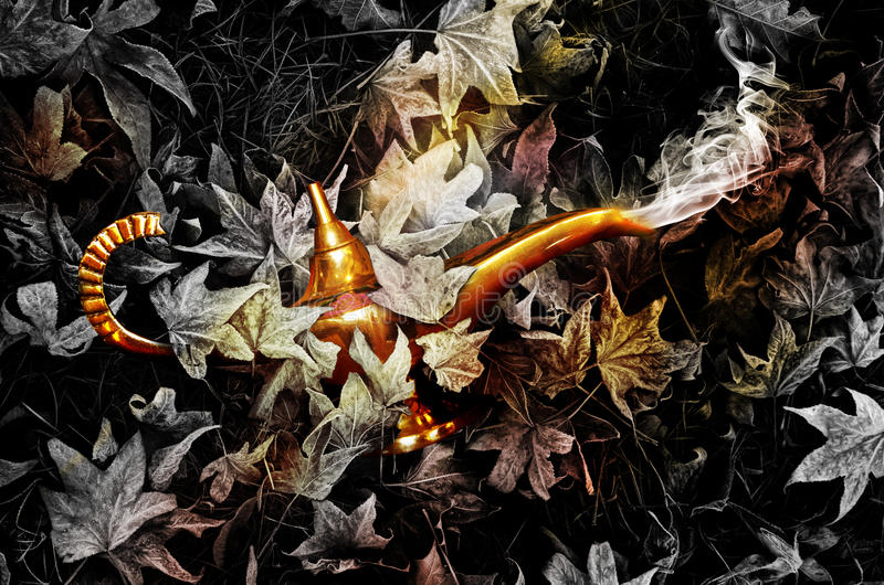 Magic golden lamp. A golden magic lamp hidden beneath leaves comes to life with smoke coming from its spout stock images