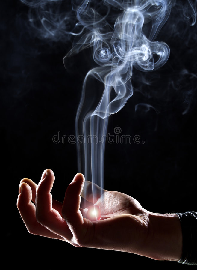 Magic hand. Holding glowing cube with ascending smoke royalty free stock photo