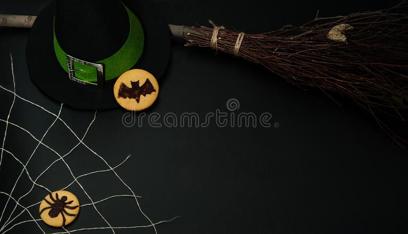 Magic hat with green ribbon and silver buckle,  homemade biscuits with a bat,  witch`s broom, spider web and cookies with a spider stock image