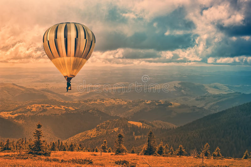 Magic journey. Unusually colored fantasy illustration of a hot air balloon flying over the mountains