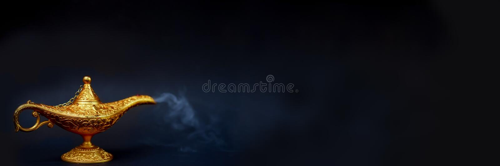 Magic lamp. A Vintage magical lamp and smoke coming out on the black background, website banner size royalty free stock photos