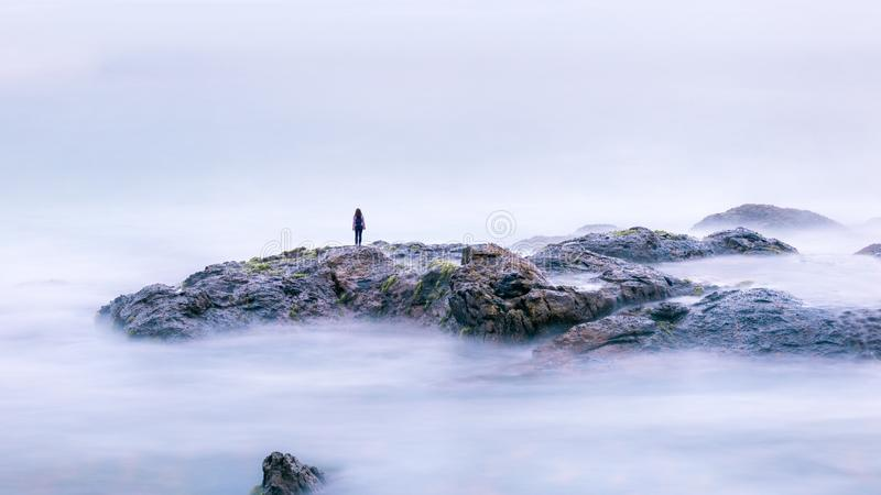 Magic landscape with lonely person and surreal rocks in sea stock photography