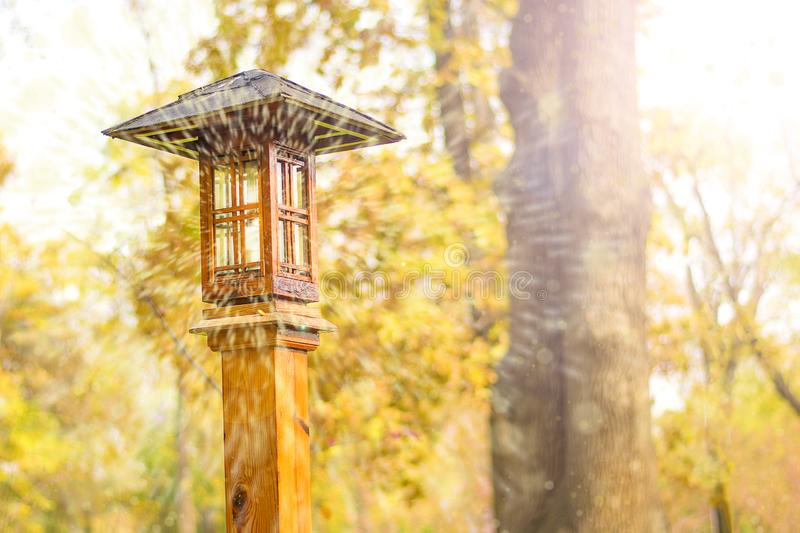 Magic light from lantern in Japanese style against  backdrop of Autumn park landscape. Orange colorful autumn trees Hello september, october, november concept royalty free stock photos