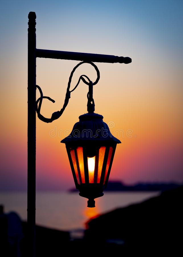 The magic light of the rising sun through the glass of a decorative lantern. Morning seascape.  royalty free stock image