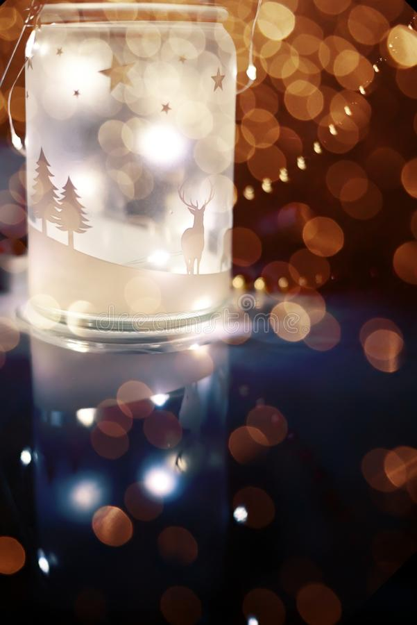 Magic luminous lantern with lights and colorful bokeh from garlands on a black background. Christmas New Year decorations and mood royalty free stock photos