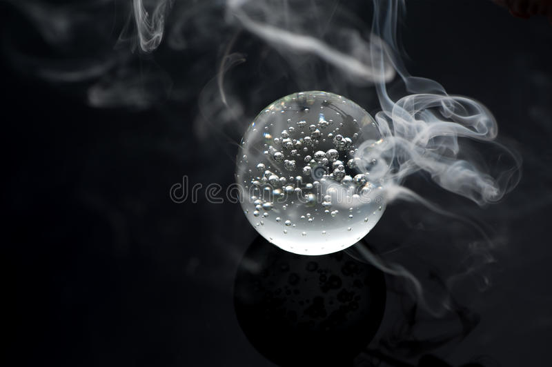 Magic Marble crystal ball and smoke. On a black background royalty free stock photo