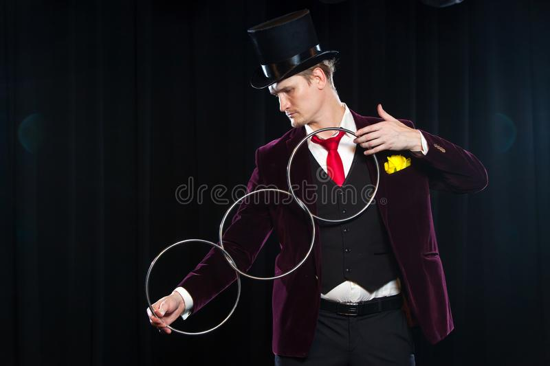 Magic, performance, circus, show concept - magician in top hat showing trick with linking rings.  royalty free stock photo