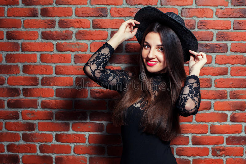 Magic is. Portrait of a young beautiful girl in black body dresses on the background of a brick wall royalty free stock photo