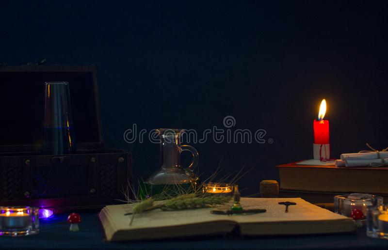 Magic potion, ancient books and candles on dark background. Fairy magic and Halloween royalty free stock photo