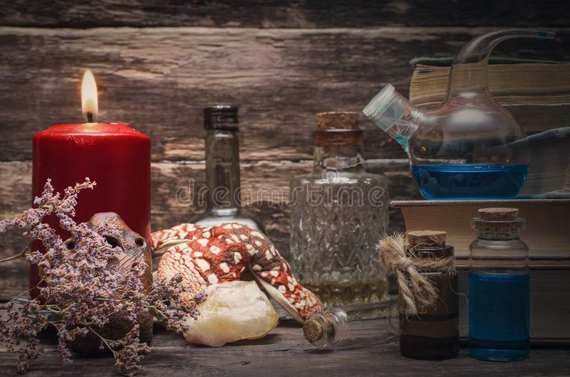 Magic potion or essential oil bottles. Magic potion in the vial on the wizard table. Witchcraft concept. Essential oil bottles and old books. Herbal medicine stock photography