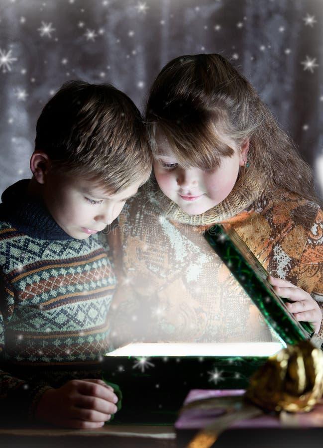 Magic present. Children opening christmas magic present stock photos